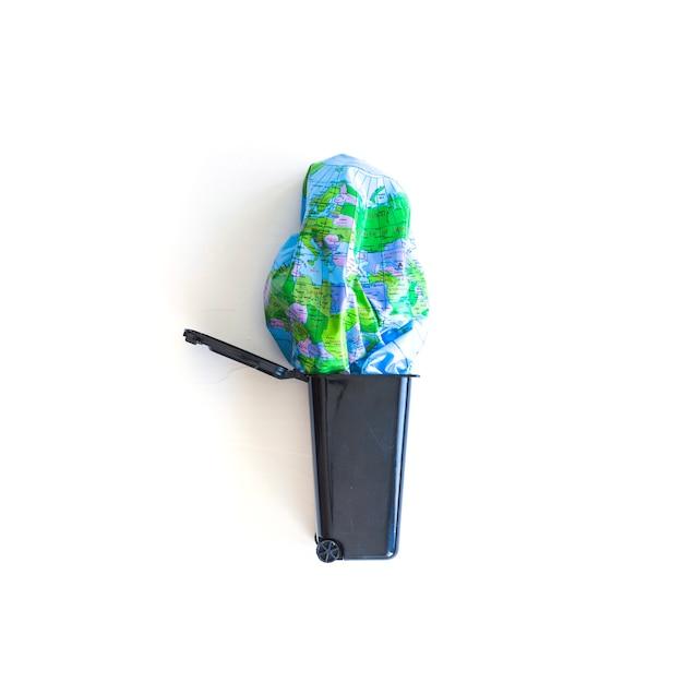Bola de terra desinflada no lixo Foto gratuita