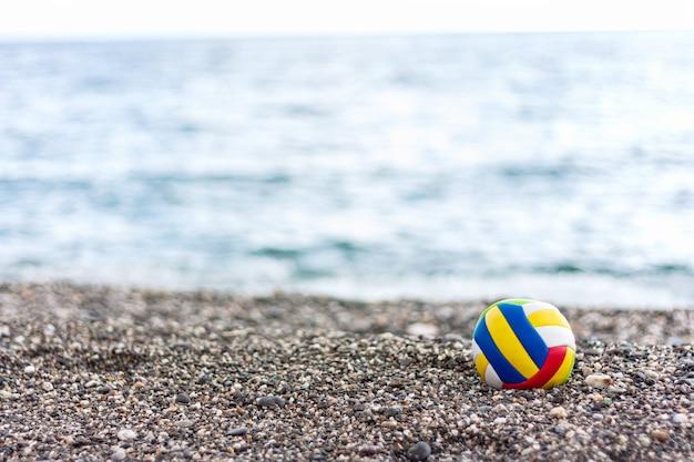 Bola infantil solitária colorida em uma praia de seixos no fundo do mar de verão. Foto Premium