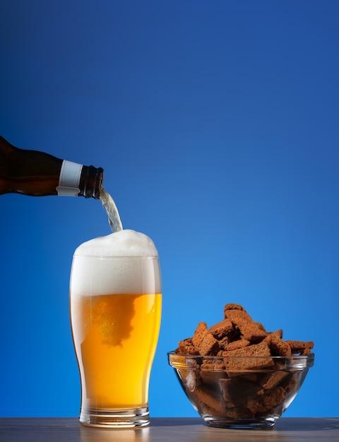 Bolachas salgadas de centeio e cerveja derramando em vidro Foto Premium