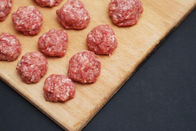 Bolas cruas de carne crua no escuro Foto Premium