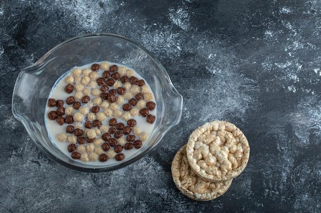 Bolas de chocolate e trigo em uma tigela de vidro com pão crocante. Foto gratuita