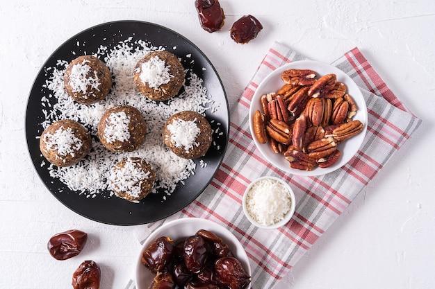 Bolas de energia orgânicas saudáveis feitas com datas, ameixas secas, passas, amendoim, com aparas de coco, em chapa preta em branco Foto Premium