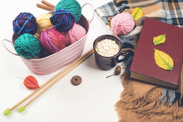 Bolas de fio de lã natural e agulhas de tricô de madeira na mesa branca Foto Premium