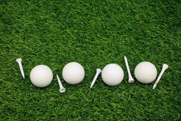 Bolas de golfe brancas e tees brancos estão na grama verde Foto Premium