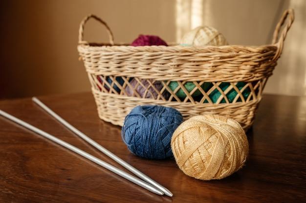 Bolas de lã deite na mesa de madeira perto com cesta de vime com agulhas de tricô Foto Premium