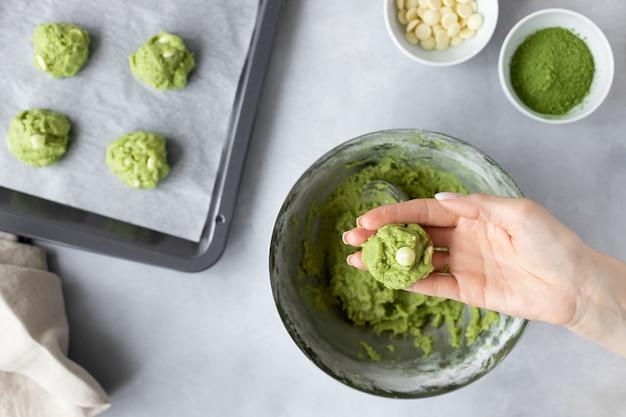 Bolas de massa de biscoito de chá verde matcha em mão feminina Foto Premium