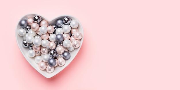 Bolas de natal brancas, rosa, cinza em forma de coração na rosa. vista do topo. banner de natal. . Foto Premium