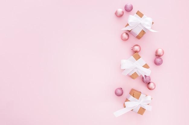 Bolas de natal e presentes em um fundo rosa Foto gratuita