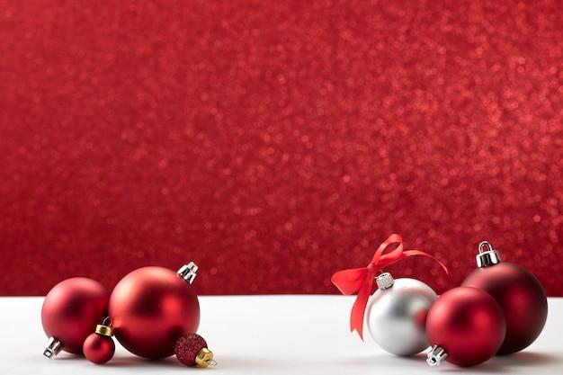 Bolas de natal na parede branca de mesa vermelha Foto Premium