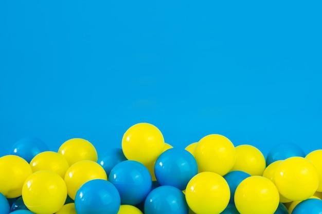 Bolas de plástico amarelas e azuis na piscina da sala de jogos Foto Premium