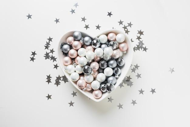 Bolas de prata brancas, rosa, cinza de natal em forma de coração em fundo rosa decorado conceito de estrelas de confetes. Foto Premium