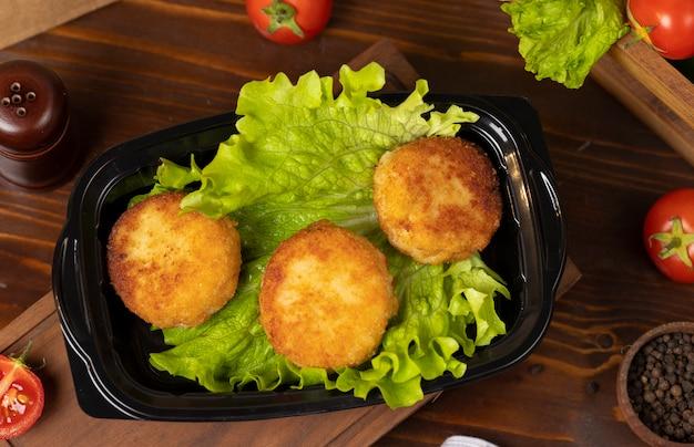 Bolas de queijo frito assado com batata recheada com queijo e carne takeaway Foto gratuita