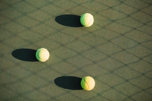 Bolas de tênis no campo de tênis e sombra líquida Foto gratuita