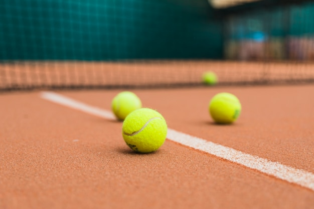 Bolas de tênis verdes na quadra perto da rede Foto gratuita