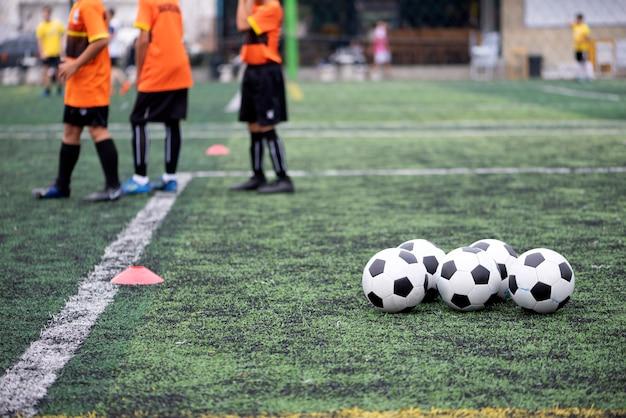 Bolas de treinamento no campo de futebol verde Foto Premium