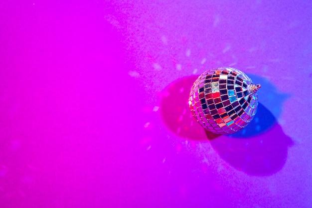 Bolas pequenas brilhantes do disco que sparkling em uma luz roxa bonita. conceito de festa de discoteca Foto Premium