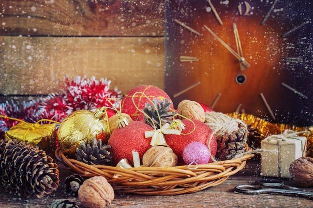 Bolas vermelhas e amarelas da composição do natal, cones, pulso de disparo velho em uma cesta em de madeira. estilo do vintage. tonificação Foto Premium
