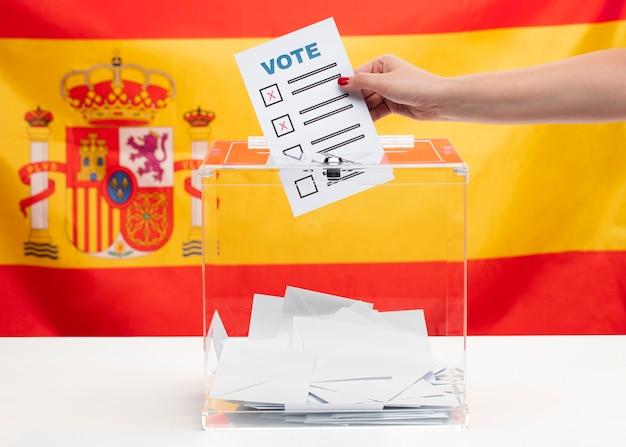 Boletim de voto e caixa no fundo da bandeira espanhola Foto gratuita