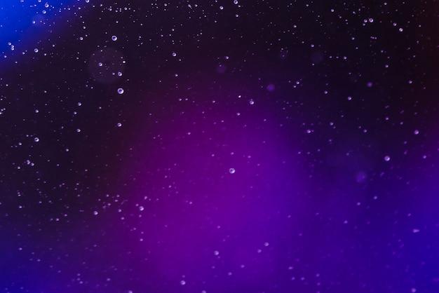 Bolhas de ar minúsculas abstratas em fluido no fundo gradiente desfocado Foto gratuita