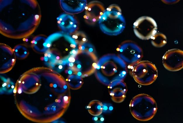 Bolhas de sabão coloridas flutuam no escuro Foto Premium