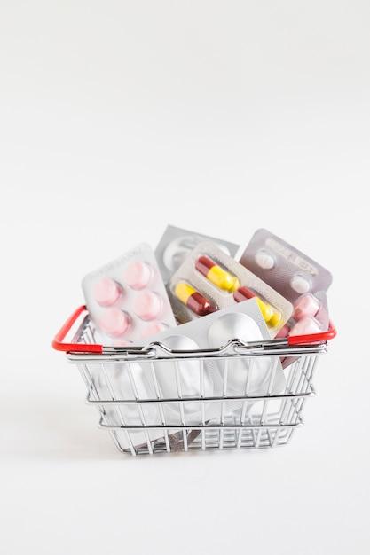 Bolhas diferentes da medicina na cesta de aço inoxidável no fundo branco Foto gratuita