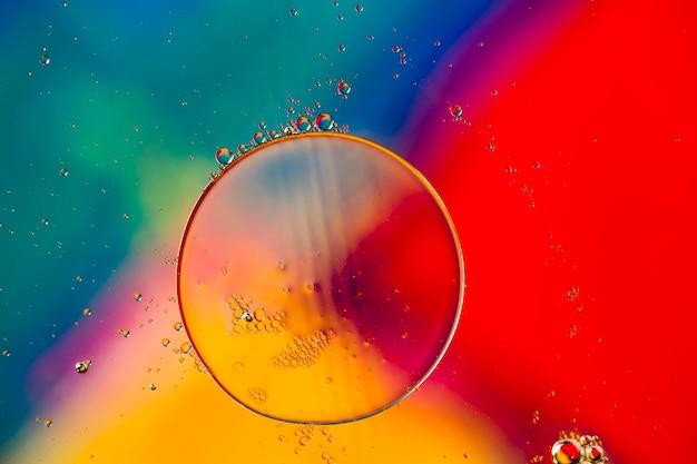 Bolhas oleosas de close-up e gotas no cenário aquoso colorido Foto gratuita