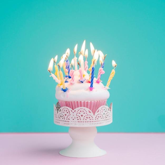 Bolinho de aniversário saboroso com velas coloridas Foto gratuita