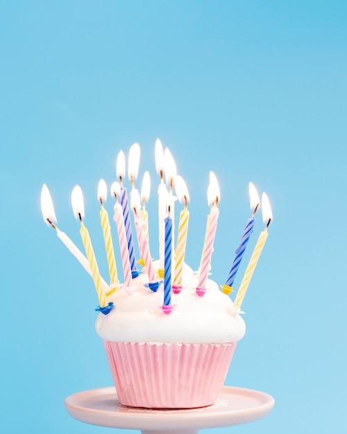 Bolinho de aniversário saboroso sobre fundo azul Foto gratuita