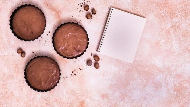 Bolinho de chocolate; bloco de notas de avelã e espiral no plano de fundo texturizado Foto gratuita