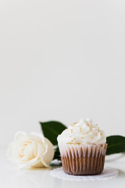 Bolinho de creme chicoteado com rosa branca, isolado no fundo branco Foto gratuita