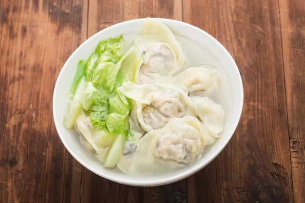 Bolinho de massa chinês wonton em sopa clara Foto Premium