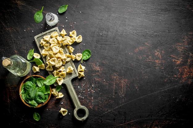 Bolinho de massa cru com carne e folhas de espinafre em uma tigela Foto Premium