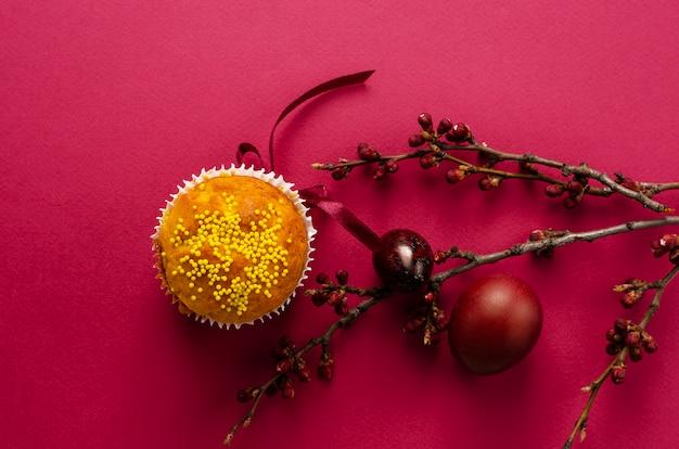 Bolinho de páscoa decorado com fita e polvilha, ovos coloridos Foto Premium