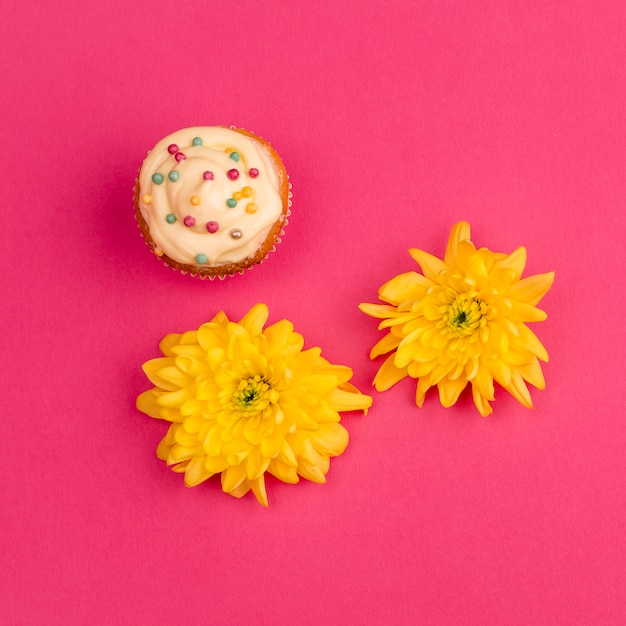 Bolinho doce perto de botões de flores Foto gratuita