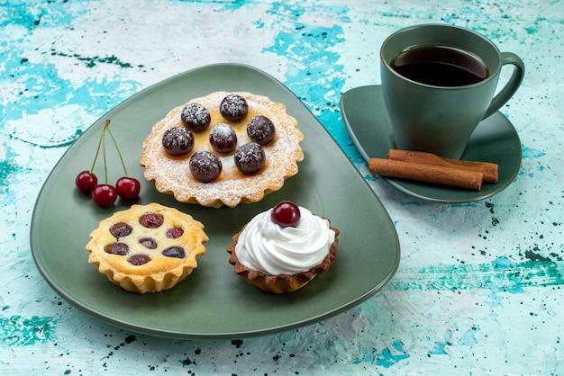 Bolinhos com frutas dentro do prato verde junto com chá e canela no azul, bolo doce de chá assar torta Foto gratuita
