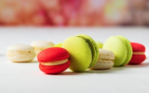 Bolinhos de amêndoa franceses doces e coloridos na bandeira colorida do fundo com espaço da cópia. Foto Premium