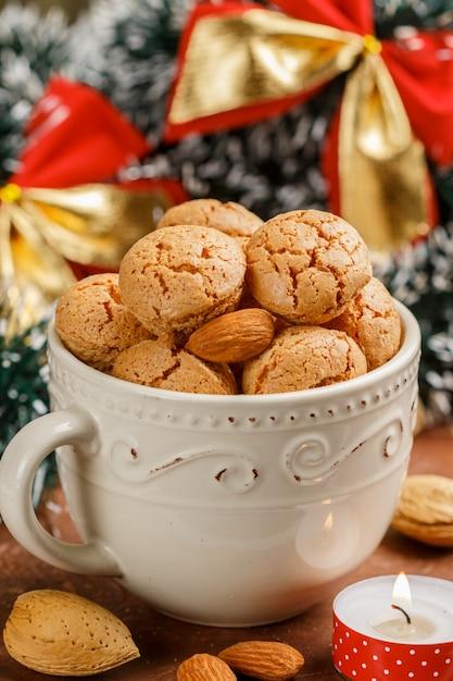 Bolinhos de amêndoa italianos tradicionais em um copo leve. biscoitos amaretti. natal e ano novo Foto Premium