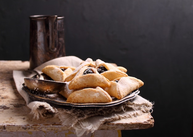 Bolinhos de hamantaschen com semente de papoula e risins e açúcar de confeiteiro em um prato, cozido para o festival judaico de purim. Foto Premium