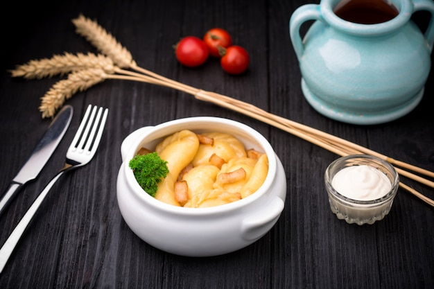 Bolinhos de massa com batatas e cracknel em fundo preto de madeira Foto Premium