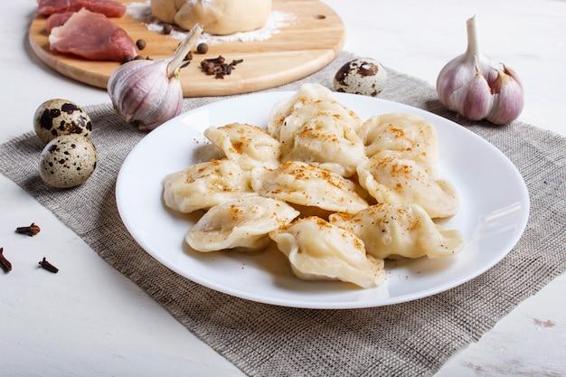 Bolinhos de massa com ingredientes (carne, massa, especiarias) em uma toalha de linho branco Foto Premium