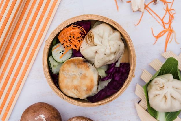 Bolinhos de massa e salada no vapor no pano de fundo Foto gratuita