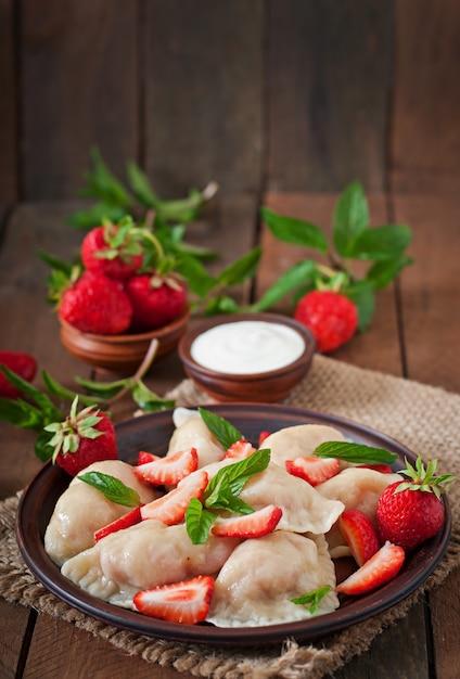 Bolinhos de massa frescos com morangos e creme de leite Foto Premium