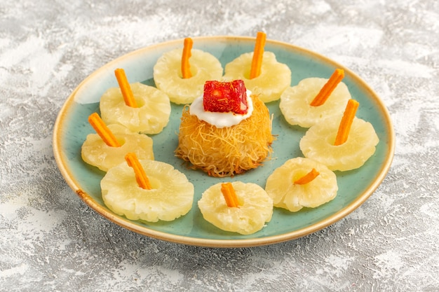 Bolinhos de massa oriental dentro do prato com anéis de abacaxi seco com creme branco Foto gratuita