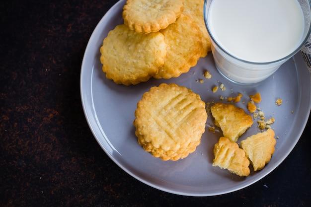 Bolinhos de shortbread de açúcar doce caseiro com leite no fundo de mesa de concreto de pedra escura Foto Premium