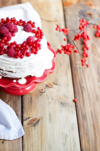 Bolo branco com frutas vermelhas e um galho em uma mesa de madeira Foto Premium