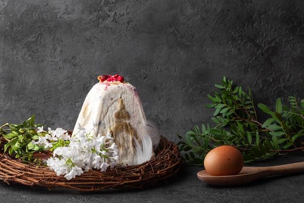 Bolo branco de kulich da páscoa, ovo marrom e folhas Foto Premium