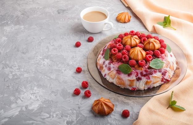 Bolo caseiro de geléia com leite, biscoitos e framboesa com xícara de café e têxtil laranja, vista lateral. Foto Premium