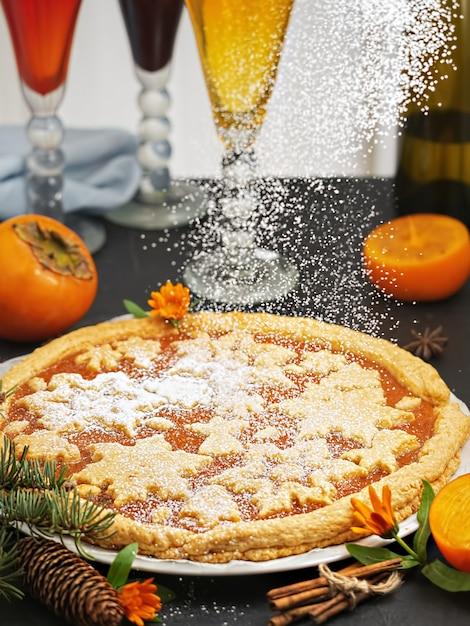 Bolo caseiro festivo com geléia de caqui. o bolo é decorado com figuras de natal de biscoitos. ao lado da torta são fatias de caqui e uma árvore de natal. fechar-se. Foto Premium