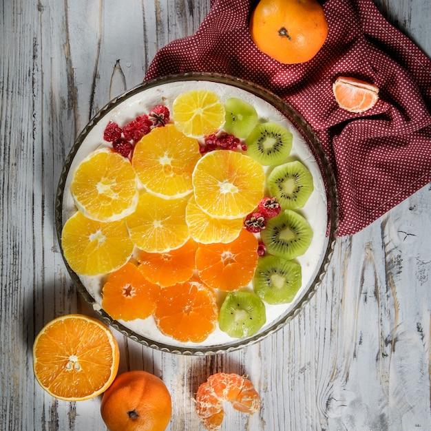 Bolo com kiwi, frutas cítricas, framboesa em um prato Foto gratuita
