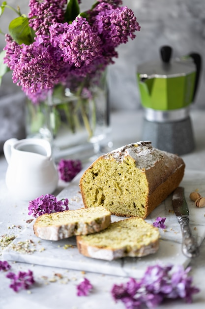 Bolo com pistache e espinafre com uma xícara de café com um buquê de lilases na mesa. copie o espaço Foto Premium